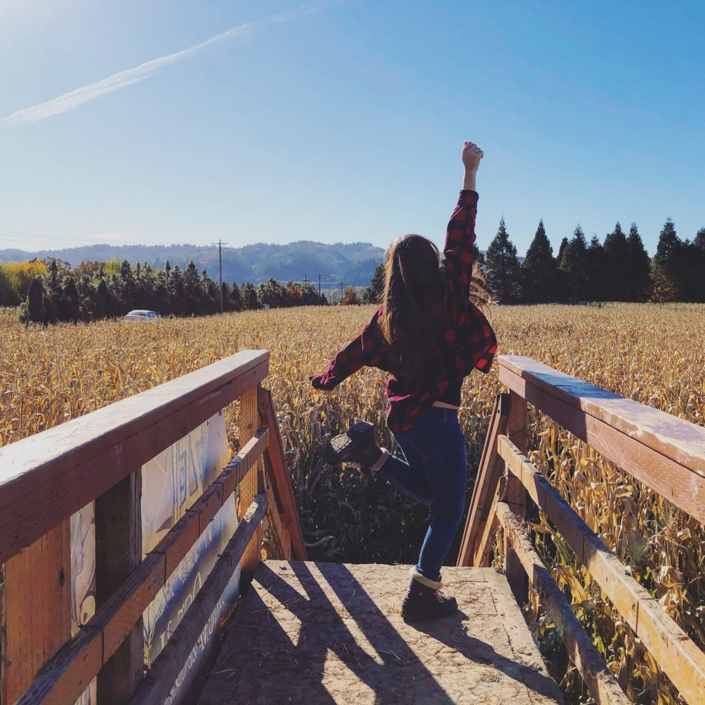 girl pumping fist in the air on top of a wooden bridge in a corn maze
