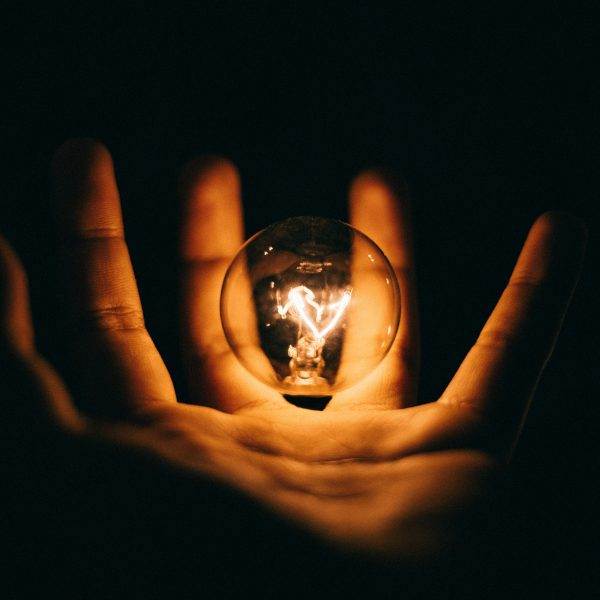 A hand holding a lit lightbulb on a dark backdrop