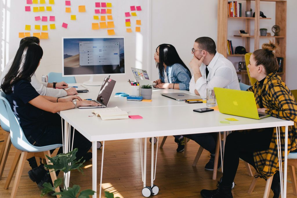 five members of a small business team sitting around a white table with laptops looking at presentation monitor and sticky notes on the back wall