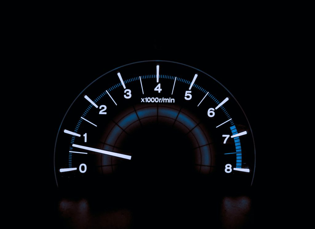 lighted speed dial for car showing increasing speed to faster driving, set on black background