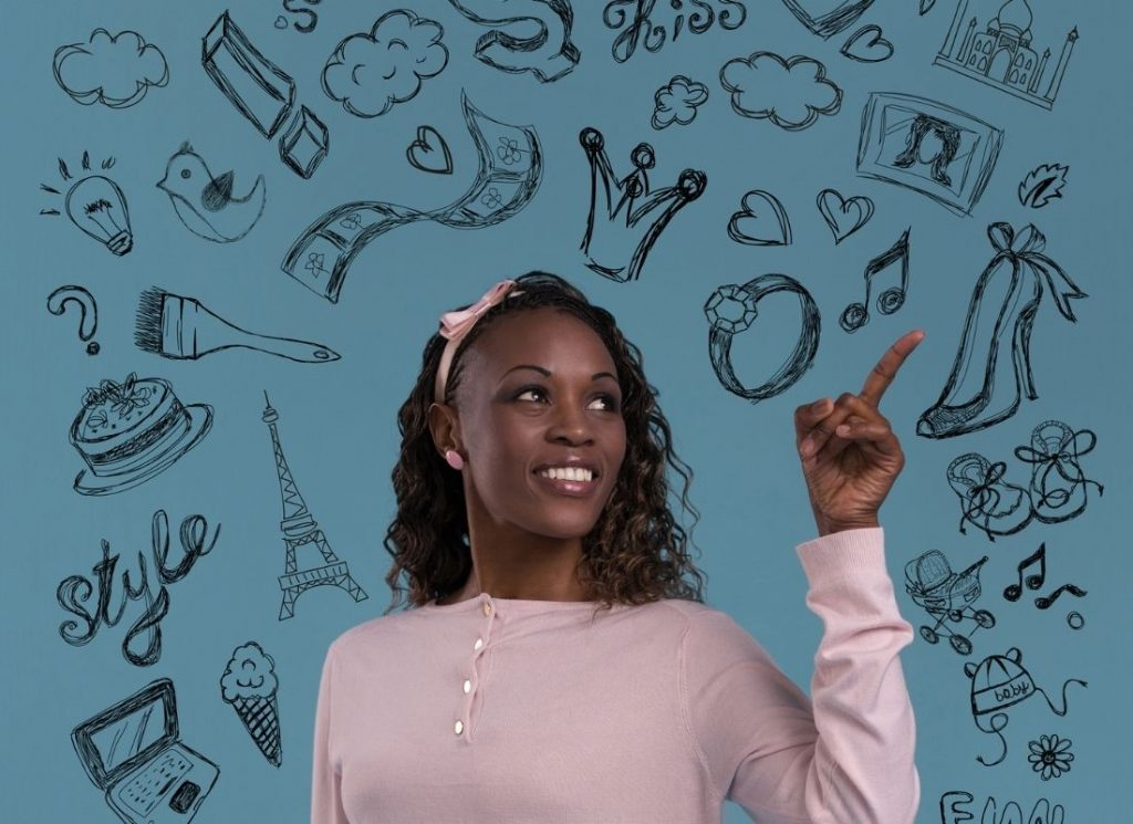Black woman in pink outfit and hair bow pointing above to buyer persona values dreams and needs for purchasing journey