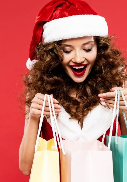 Red haired female holiday custome rin Santa hat against red background holding three shopping bags