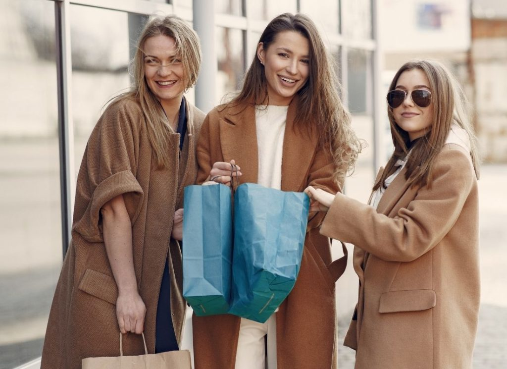 Three girls standing with blue shopping bags and brown overcoats in front of urban building background