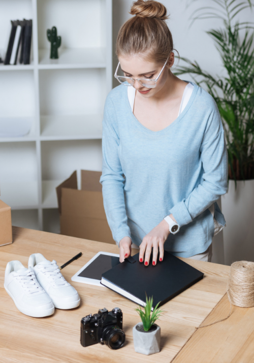Blonde female with high bun and blue sweater packaging shoe orders for holiday customers in her office