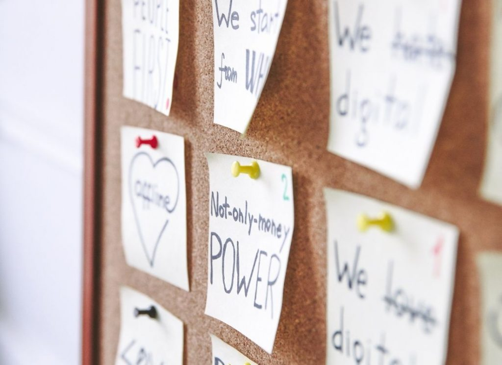 sticky notes with push pins on a corkboard