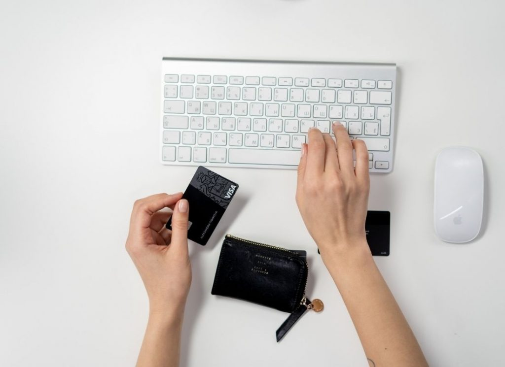 aerial shot of hands typing and holding credit card on white keyboard and desk while holiday shopper purchases online