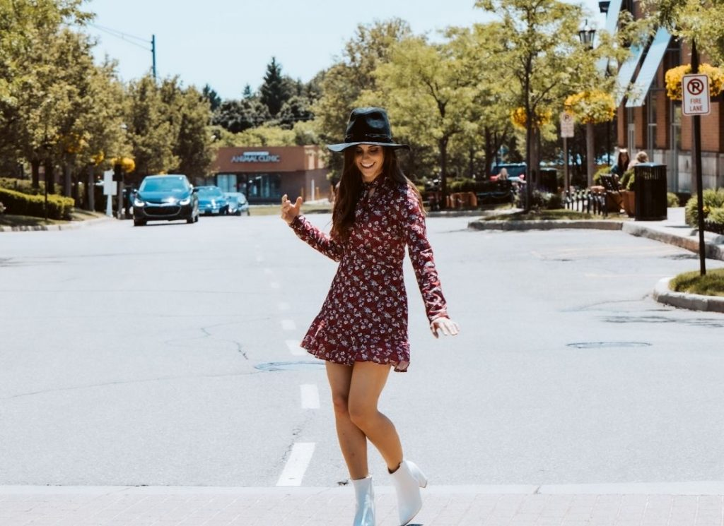 brunette female brain based coach in black hat, red flowered dress and white boots on a sidewalk in a street with greenery and city block background