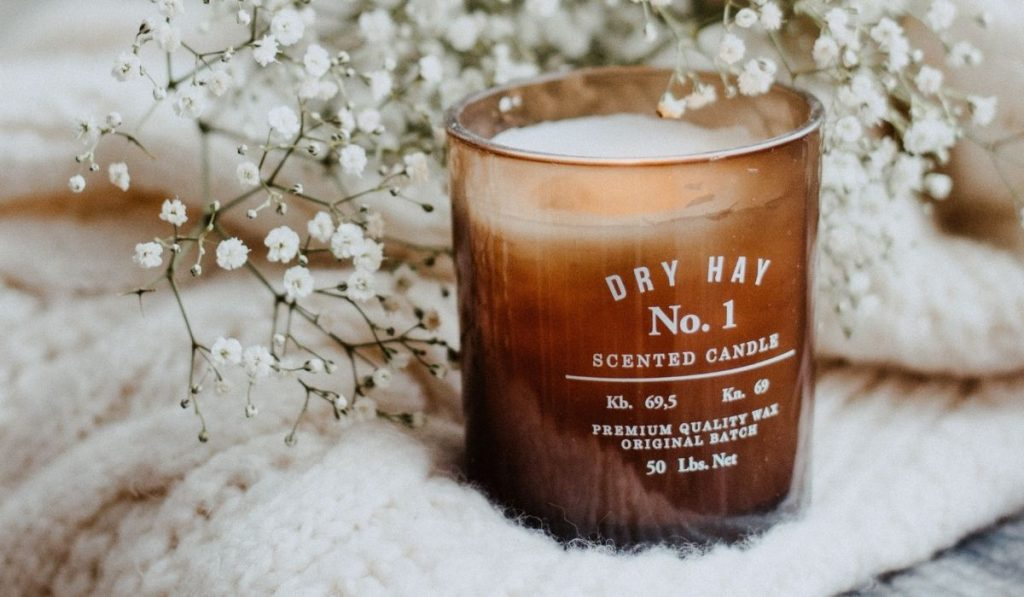 tan candle in dry hay scent with baby's breath white flowers on a white fleece swearter