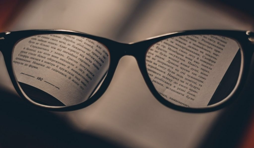 reading glasses hovering over book and magnifying text copy